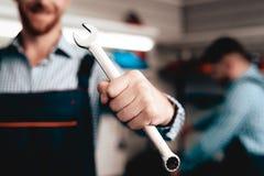 Auto mekaniker Posing With Wrench Tjänste- station royaltyfria bilder