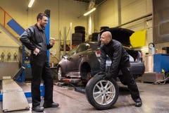 Auto mekaniker som ändrar bilgummihjul på seminariet Arkivbilder