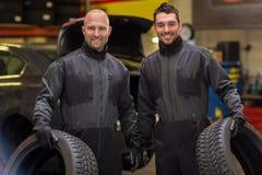 Auto mekaniker som ändrar bilgummihjul på seminariet Royaltyfri Foto