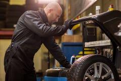 Auto mekaniker som balanserar bilhjulet på seminariet Royaltyfria Bilder