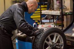 Auto mekaniker som balanserar bilhjulet på seminariet Royaltyfri Fotografi