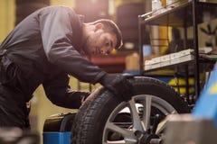 Auto mekaniker som balanserar bilhjulet på seminariet Arkivfoto