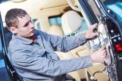 Auto mekaniker som förlägger de fuktande matsna på bildörr Arkivbild