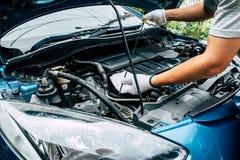 Auto mekaniker som kontrollerar den olje- nivån i bilmotor arkivbilder