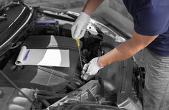 Auto mekaniker som kontrollerar den olje- nivån i bilmotor royaltyfri bild