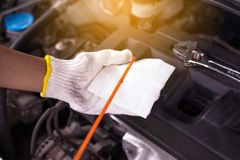 Auto mekaniker som kontrollerar motorn för olje- nivå, automatisk underhållsbilreparation royaltyfria bilder
