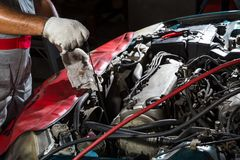 Auto mekaniker som kontrollerar olja, bilreparationsservice arkivfoton