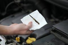 Auto mekaniker som kontrollerar oljestickan för motorolja i bil Arkivfoton