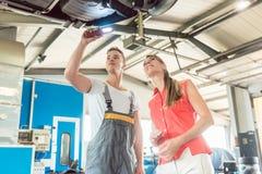 Auto mekaniker som kontrollerar rotorerna f?r skivabroms av bilen av en kvinnlig kund arkivfoton