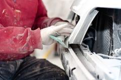 Auto mekaniker som prepairing den främre stötdämparen av en bil arkivbilder