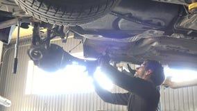 Auto mekaniker som reparerar bilen mot intensivt fönsterljus lager videofilmer