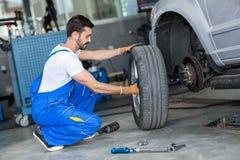 Auto mekaniker som tar bort hjulet av en bil fotografering för bildbyråer