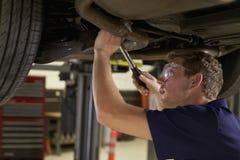 Auto mekaniker Working Underneath Car i garage arkivbild