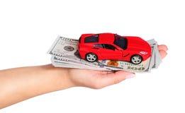 Auto met contant geld in vrouwelijke die hand op witte achtergrond wordt geïsoleerd Stock Foto