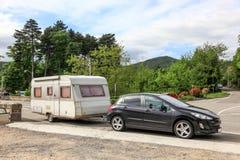 Auto met een caravan op de weg Stock Foto