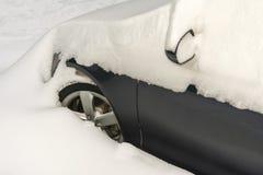 Auto met sneeuw tijdens sneeuwval in het Parkeerterrein wordt behandeld dat stock afbeelding