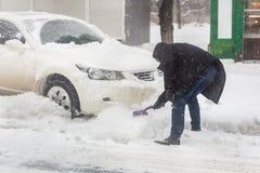 Auto met sneeuwafwijking wordt geblokkeerd op stadsstraat die Mensen schoonmakend voertuig van sneeuw met borstel tijdens zwaar s stock fotografie