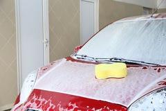 Auto met spons op zijn bonnet stock foto