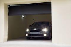 Auto met zijn lichten in de garage stock afbeeldingen