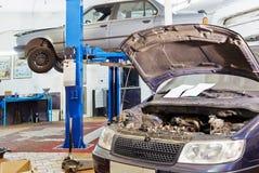 Auto mit offener Haube und Auto auf Auto heben an Lizenzfreies Stockfoto