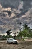 Auto mit Wolken mittleren Tag lizenzfreies stockbild