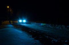 Auto nachts auf der schneebedeckten Straße Stockbilder