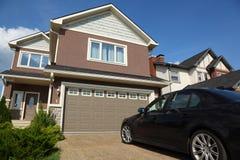 Auto nahe Garage des neuen zwei-sagenumwobenen Häuschens Lizenzfreie Stockbilder