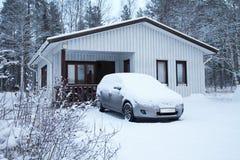 Auto onder sneeuw dichtbij wit huis stock afbeeldingen