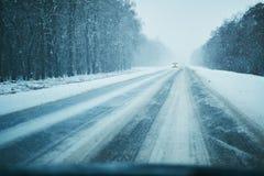 Auto in onweer op een de winterweg met verkeer Gevaar het drijven in de winter Eerste persoonsmening stock afbeelding
