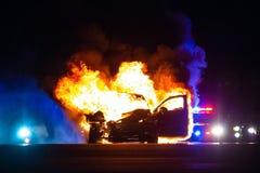 Auto op brand bij nacht met politielichten op achtergrond stock fotografie