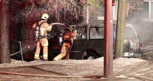Auto op brand, brandbestrijders die het uitsterven beëindigen stock video