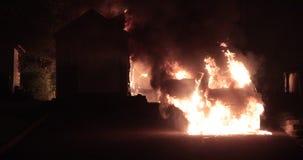 Auto op brand met een plattelandshuisje wordt gehaald dat stock footage