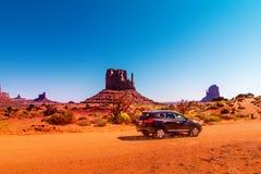 Auto op de aandrijving van de Monumentenvallei De Valleiaandrijving is een toneellandweg door het Stammenpark van Navajo tussen A Royalty-vrije Stock Afbeeldingen