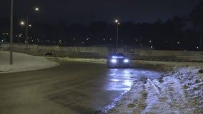 Auto op de lege sneeuwweg bij nacht met zijn koplampen wordt geparkeerd die actie Eenzame auto met neonkoplampen die zich bevinde stock afbeelding