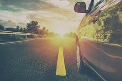 Auto op de weg bij zonsopgang stock afbeeldingen