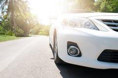 Auto op de weg met zonlicht in Kokosnotenbosje Thailand stock fotografie