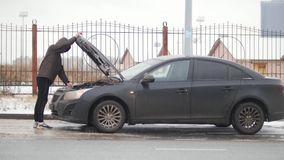 Auto op een de winterweg Autoprobleem Autoprobleem op een sneeuwlandweg Een jonge mens sluit de kap en krijgt in de auto stock footage