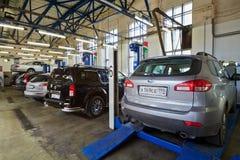 Auto op grondplaat van postlift vier in workshop Stock Foto's