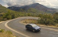 Auto op kronkelige weg in bergen Royalty-vrije Stock Foto's