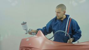 Auto painter spraying red paint on car front bumper in special booth royalty free stock photo