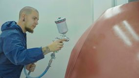 Auto painter spraying red paint on car hood in special booth stock image