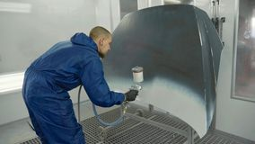 Auto painter spraying white paint on car hood in special booth stock photos
