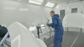 Auto painter spraying white paint on car spare fender in special booth stock images