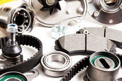 Auto parts background. Hub, pump, brake pads, filter, timing belt, rollers, constant velocity joints, thermostat and other on. White background spare new royalty free stock images