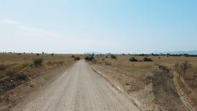 Auto podróż: SUV jedzie sawannę, dolina z górami na horyzoncie POV - Punkt widzenia samochodowy chodzenie wzdłuż drogi zbiory