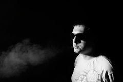 Portrait of man. In a shirt and sunglasses, on a black background, he blows the smoke, self-portrait, black and white photo Royalty Free Stock Images