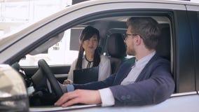 Auto przedstawicielstwo handlowe, życzliwy azjatykci żeński samochodowy sprzedaż kierownik radzi męski kupujący obsiadanie wśrodk zbiory wideo