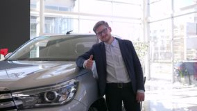 Auto purchase, young buyer man with glasses gladly strokes new car and gives positive gesture. In showroom stock video
