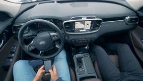 Auto que conduz carros autônomos do piloto automático Agitar a roda está girando quando dois pessoas se sentarem em um veículo vídeos de arquivo