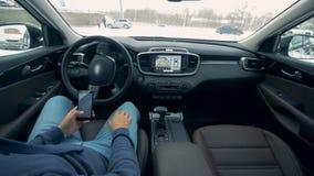 Auto que conduz carros autônomos do piloto automático O motorista masculino com um telefone está estacionando um carro que seja c video estoque
